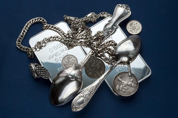 Hopean hintaa maksetaan erilaisista hopeaesineistä. Kuvassa hopeaharkkoja, hopea-aterimia, hopeakoruja ja hopeakolikoita.